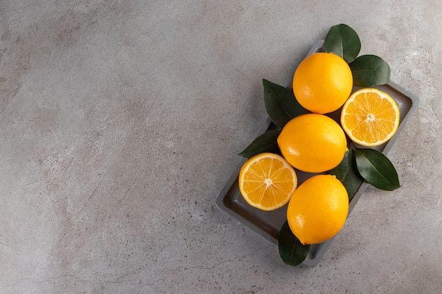 Whole and sliced lemons with leaves placed on board.