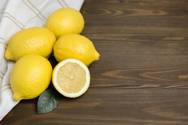 Whole and sliced lemons with white fabric on brown wooden background