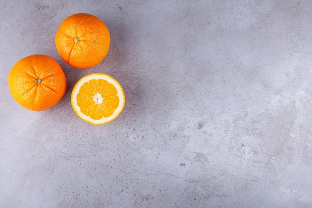 Whole and sliced orange fruits placed on a stone background .