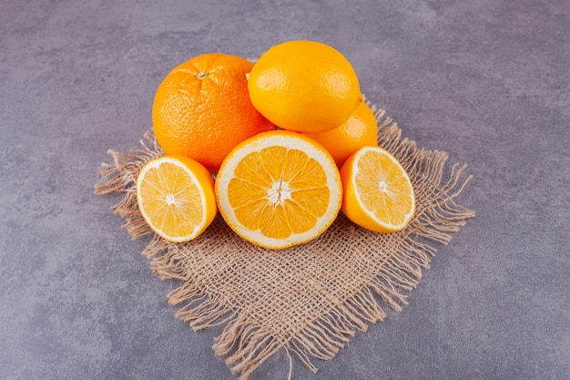 Whole and sliced orange fruits with fresh lemons placed on a sackcloth surface .