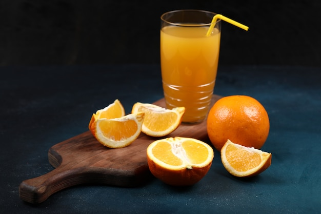 Whole and sliced oranges with a glass of juice.