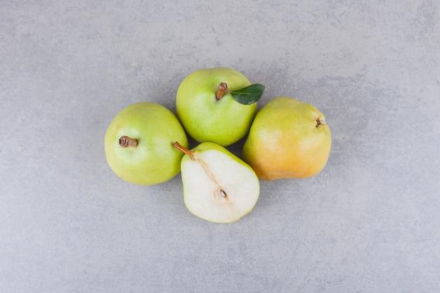 Frutti di pera interi e affettati con foglie poste su un tavolo scuro.