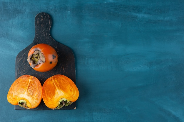 Whole and sliced persimmon fruit placed on a dark wooden board .