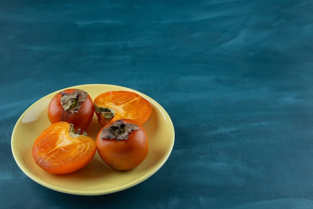 Whole and sliced persimmon fruit placed on a yellow plate .
