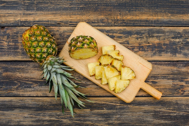 Whole and sliced pineapple in a cutting board top view on a wood grunge surface