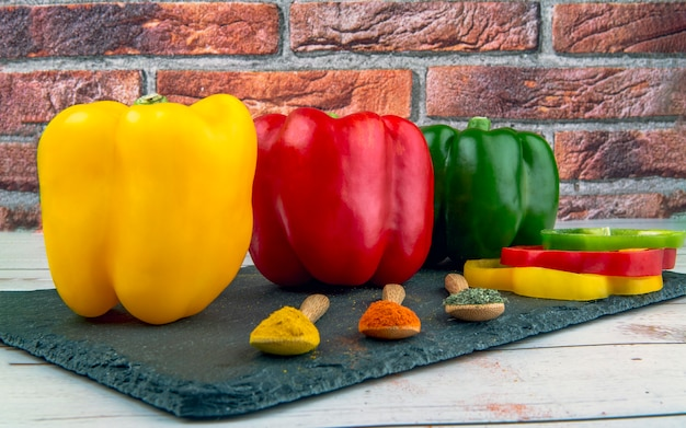 Whole and sliced red green yellow peppers and three wooden spoons with spices on black stone board