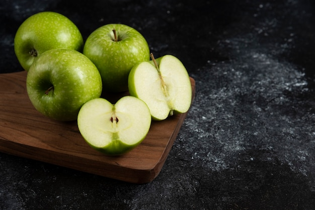 Whole and sliced ripe green apples on wooden board.