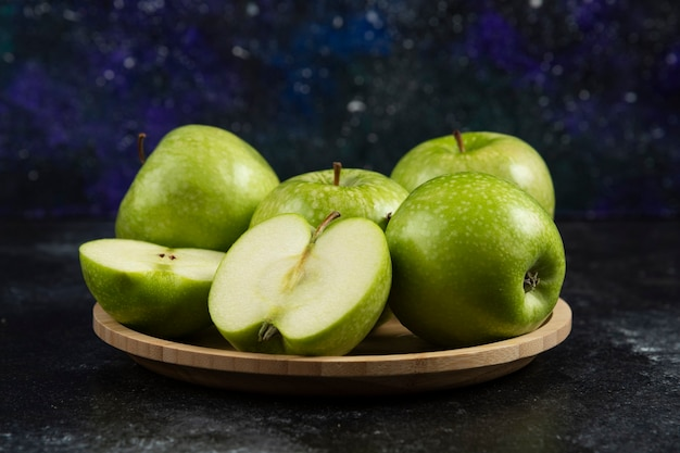 Mele verdi mature intere e affettate sul piatto di legno.