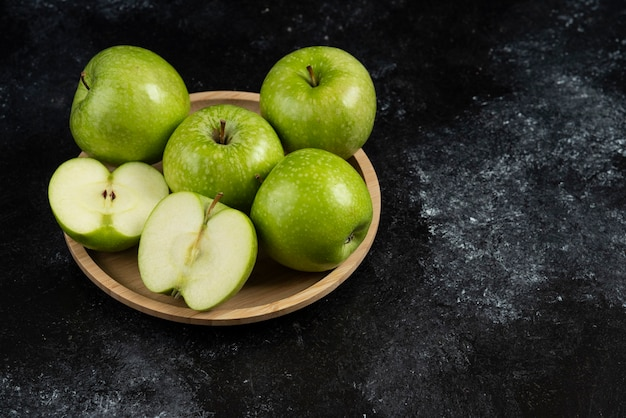 Whole and sliced ripe green apples on wooden plate.