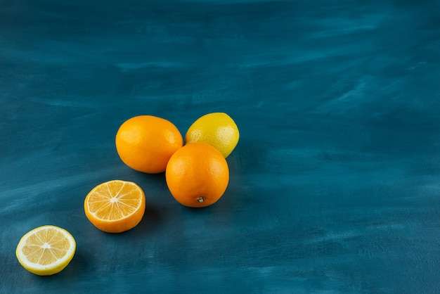 Whole and sliced ripe lemons placed on marble surface.