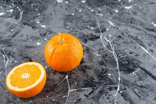 Arance mature intere ed affettate poste sulla superficie di marmo.