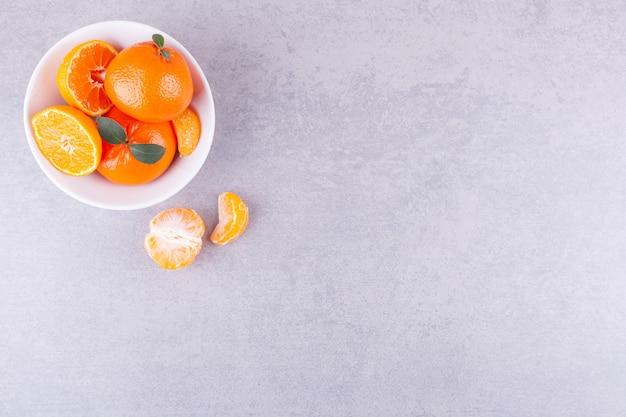 Frutti di mandarino interi e affettati con foglie poste su un tavolo di pietra.