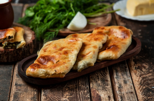 Whole and sliced vegetable pide, bread in a rustic plate on the wooden table with herbs and onion.
