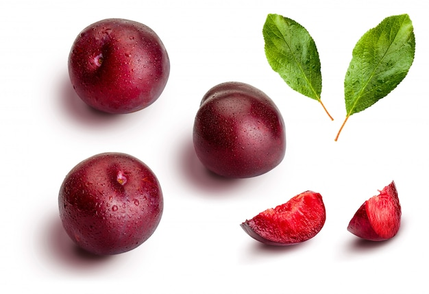 Whole and slices of plums on white background