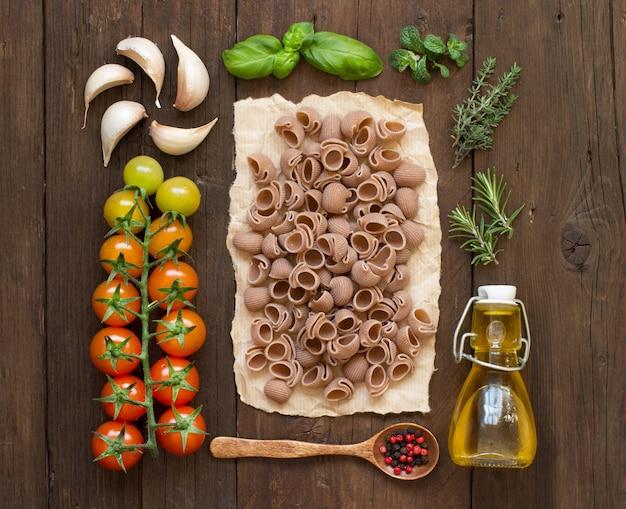 木製の表面にスペルト小麦のパスタ、野菜、ハーブ、オリーブオイル全体