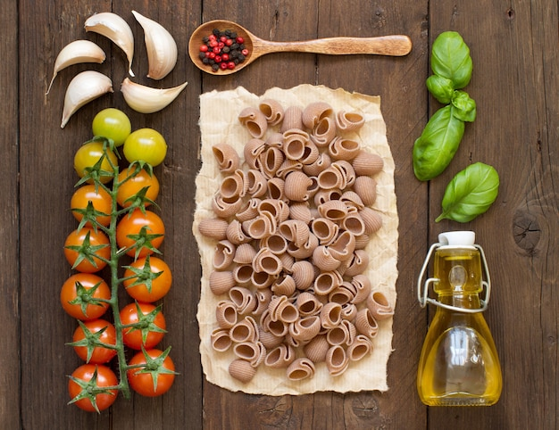 Whole spelt pasta, vegetables,  herbs and olive oil on wooden background