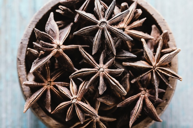 Whole star anise in a bowl on blue wood