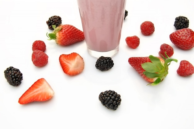 Whole strawberries, blackberries and raspberries on white background