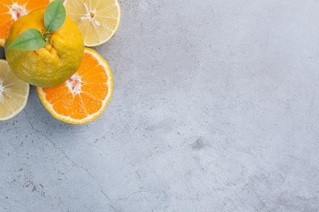 レモンのタンジェリン全体と大理石の背景のタンジェリンスライス。