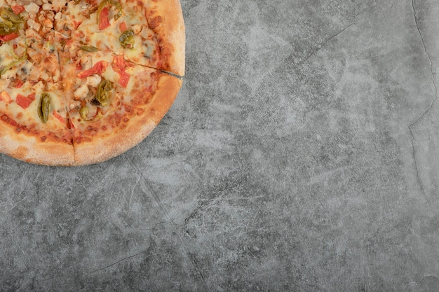 Whole tasty chicken pizza placed on stone background.