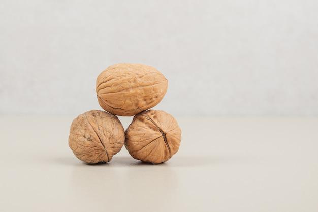 Целых три здоровых грецких ореха на белом.