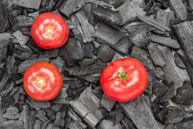 木炭に丸ごとトマト。グリル料理。有機性健康な栄養物。