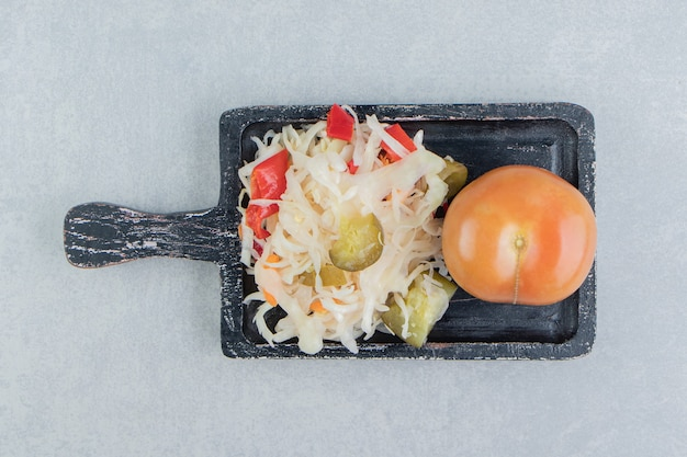 Whole tomatoes and sauerkraut on the board
