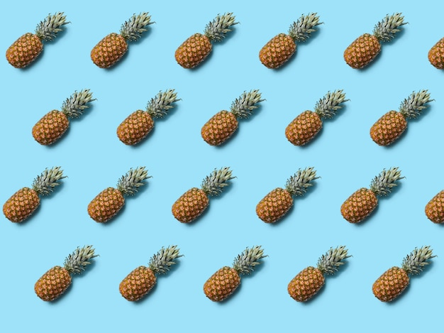 Whole tropical pineapple fruit with green leaves on blue wall. food layout. flat lay