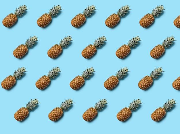 파란색 벽에 녹색 잎 전체 열 대 파인애플 과일. 음식 레이아웃. 플랫 레이