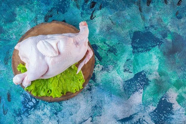 ボード上の未調理の鶏肉とレタスの葉全体