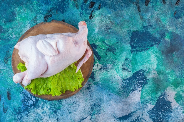 Pollo intero crudo e foglie di lattuga su un tagliere
