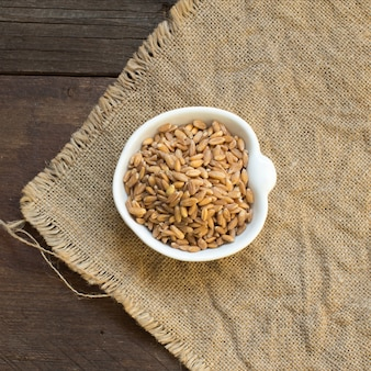 Whole unpolished spelt in a bowl top view on burlap on a wooden table