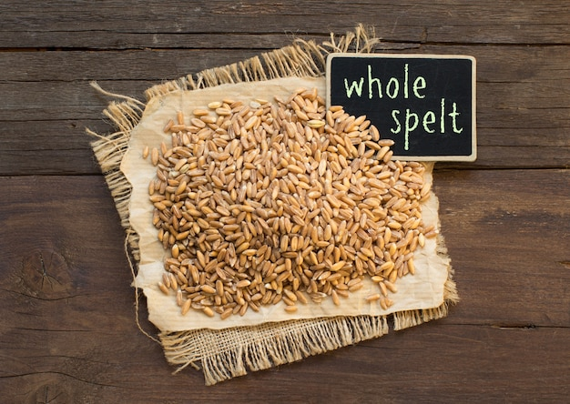 Whole unpolished spelt in a with a small chalkboard on wood