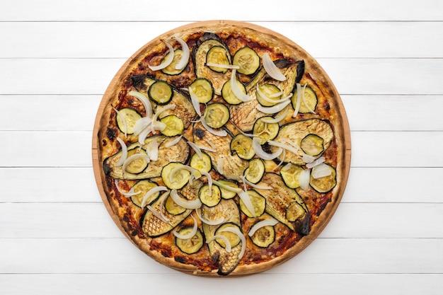 ホワイトボードの背景に木のプレートの上面図に焼きナスのズッキーニとタマネギをトッピングした全菜食主義のピザ