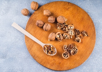 Whole walnuts and kernel on wooden spoon and board on backdrop