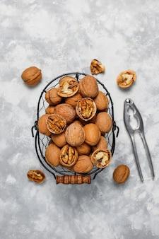 Целые грецкие орехи в скорлупе в пищевой металлической корзине, ядра грецких орехов. вид сверху на бетон