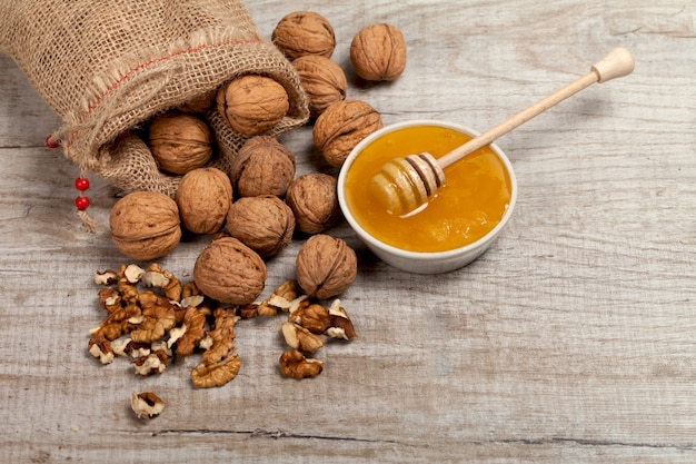 Whole walnuts, kernels and honey on the table