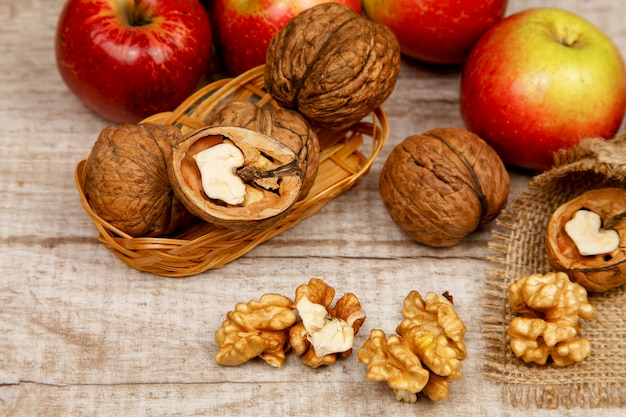 Whole walnuts and kernels on a table with apples