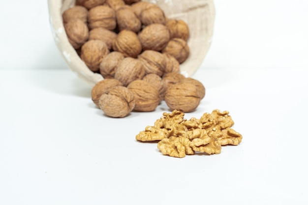 Whole walnuts and kernels on white background