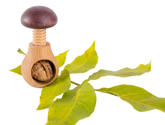 Whole walnuts and wooden screw nutcracker isolated on white background.