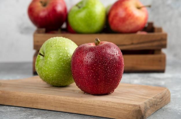 木製のまな板に全体が濡れた緑と赤のリンゴ。
