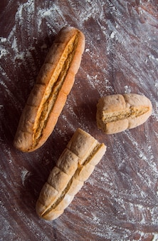 Whole wheat baguette on wooden table top view