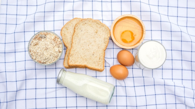 Whole wheat bread, oat, chicken egg, yogurt and milk on a table.