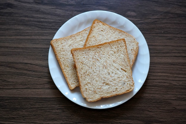 Whole wheat bread on a plate on wooden background