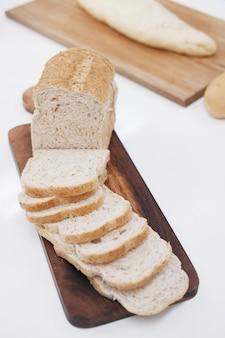 全粒粉パンのスライスが木を切っています。朝食のメニューのためのおいしくて健康的なペストリーのために自家製。