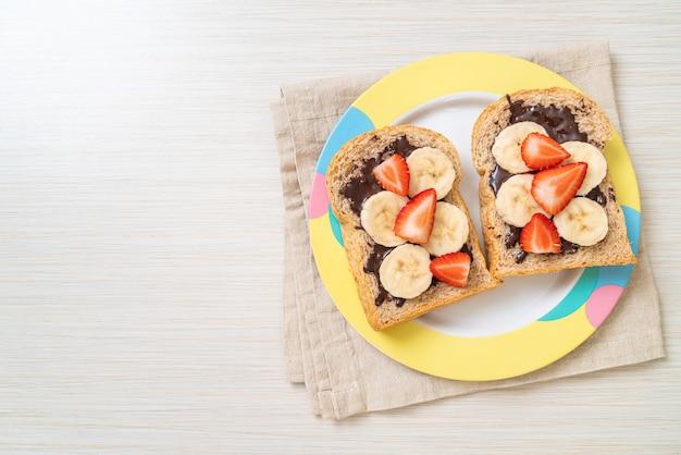 朝食に新鮮なバナナ、イチゴ、チョコレートで焼いた全粒粉パン