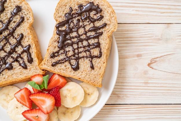 Цельнозерновой хлеб, обжаренный со свежим бананом, клубникой и шоколадом на завтрак