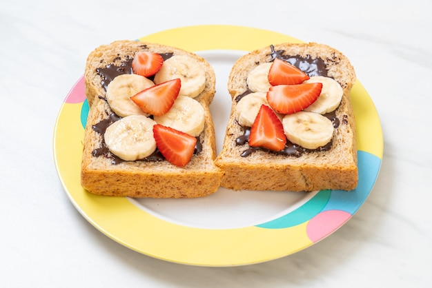 Whole wheat bread toasted with fresh banana, strawberry and chocolate for breakfast