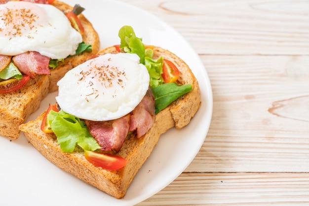 朝食に野菜、ベーコン、卵、または卵のベネディクトでトーストした全粒小麦のパン
