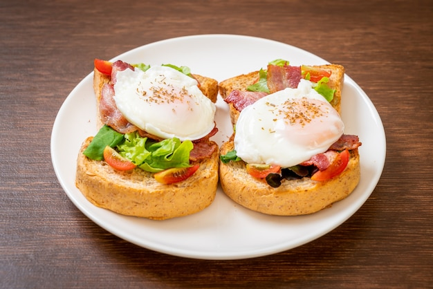 Цельнозерновой хлеб, обжаренный с овощами, беконом и яйцом или яичный бенедикт на завтрак